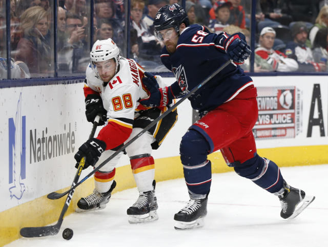 Calgary Flames' Andrew Mangiapane, left, looks for an open pass as Columbus Blue Jackets' David Savard defends during the third period of an NHL hockey game Saturday, Nov. 2, 2019, in Columbus, Ohio. (AP Photo/Jay LaPrete)