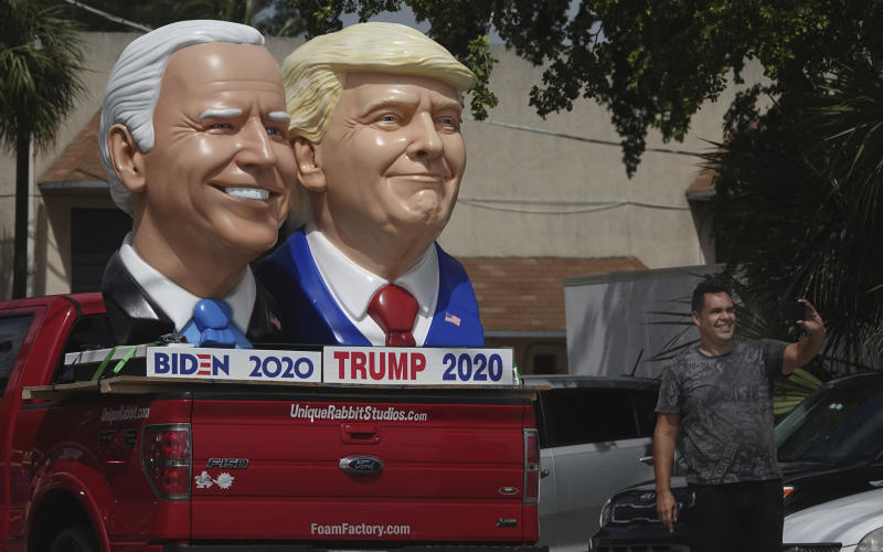 A passerby stops to take a selfie with foam sculpture depictions of President Donald Trump and Democratic presidential candidate former Vice President Joe Biden along Dixie Highway in Fort Lauderdale, Fla., Thursday, Sept. 3, 2020. (Joe Cavaretta/South Florida Sun-Sentinel via AP)