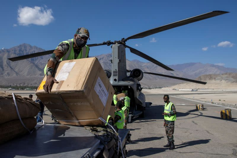 Soldiers load an Indian Air Force's Chinook helicopter with supplies at a forward airbase in Leh