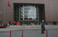 A man walks past the entrance to Istanbul's court Wednesday, Feb. 24, 2021, where the case of a Turkish private airline official and two pilots over their involvement in former Nissan Motor Co. chairman Carlos Ghosn's dramatic escape out of Japan in 2019 and to Beirut, Lebanon, was held. The court convicted a Turkish private airline official and two pilots and sentenced them each to four years and two months in prison .Ghosn, who was arrested over financial misconduct allegations in Tokyo in 2018, skipped bail while awaiting trial there. (AP Photo/Mehmet Guzel)