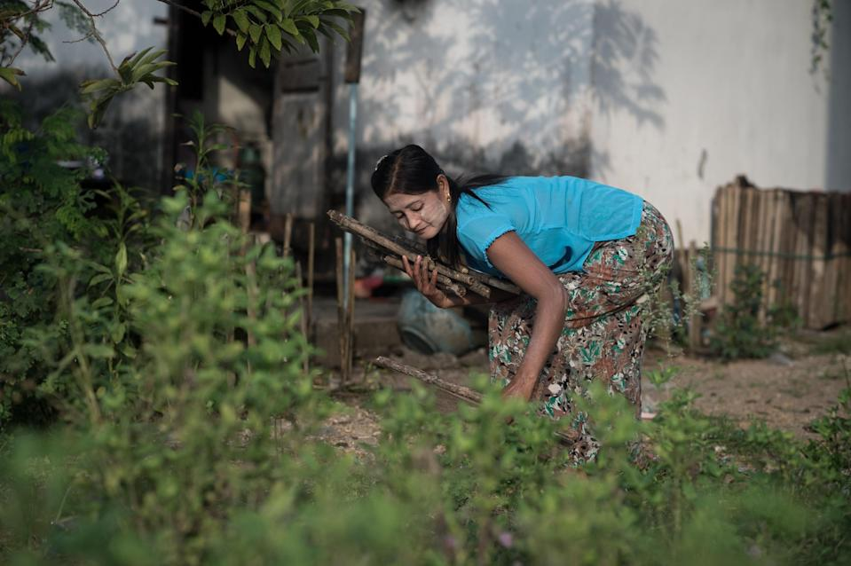 A decade after towering waves wrenched her newborn baby from her arms, Myanmar national Mi Htay collects wood in her garden outside her house in Ban Nam Khaem, Thailand, December 3, 2014 (AFP Photo/Nicolas Asfouri)