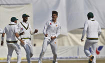 Pakistan pacer Shaheen Shah Afridi, center, celebrates with teammates after taking the wicket of Bangladesh batsman Mominul Haque during the first day of their 1st test cricket match at Rawalpindi cricket stadium in Rawalpindi, Pakistan, Friday, Feb. 7, 2020. (AP Photo/Anjum Naveed)
