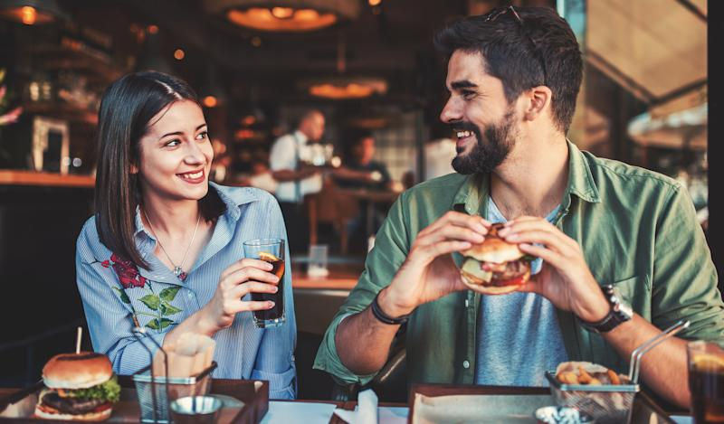 A young man and woman sit side by side smiling at each other in a restaurant. The man holds a burger, and the woman holds a drink.