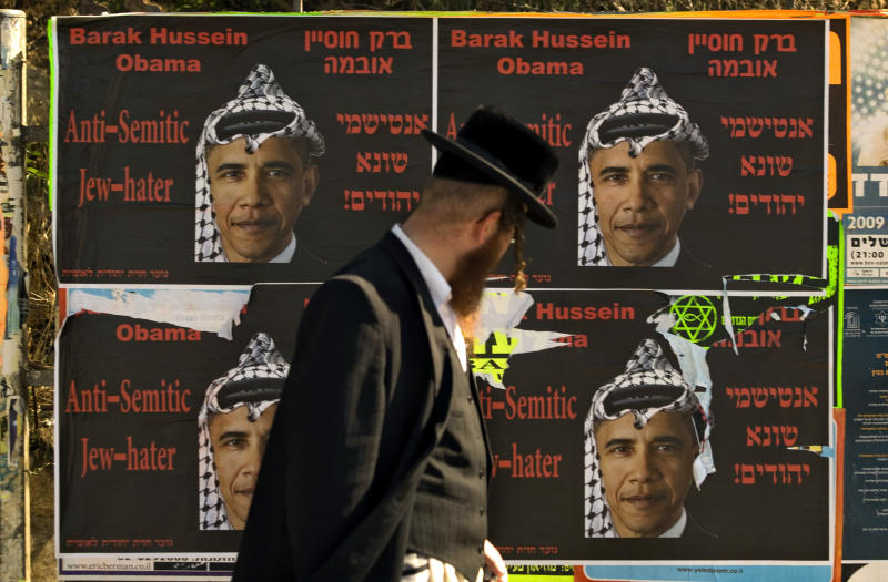 FILE -- In this Sunday, June 14, 2009 file photo, an Ultra Orthodox Jewish man walks past posters depicting US President Barack Obama wearing a traditional Arab headdress, in Jerusalem, Sunday, June 14, 2009. President Barack Obama's vow to take his message straight to the public during his first presidential visit to Israel next week will be a tough sell with many Israelis who consider him naive, too soft on the nation's enemies and even hostile to Prime Minister Benjamin Netanyahu. (AP Photo/Sebastian Scheiner, File)