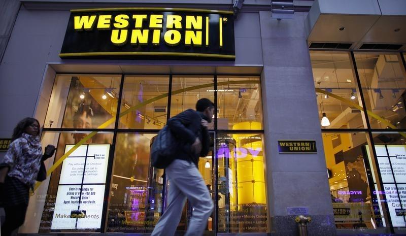 People walk past a Western Union branch at Times Square in New York