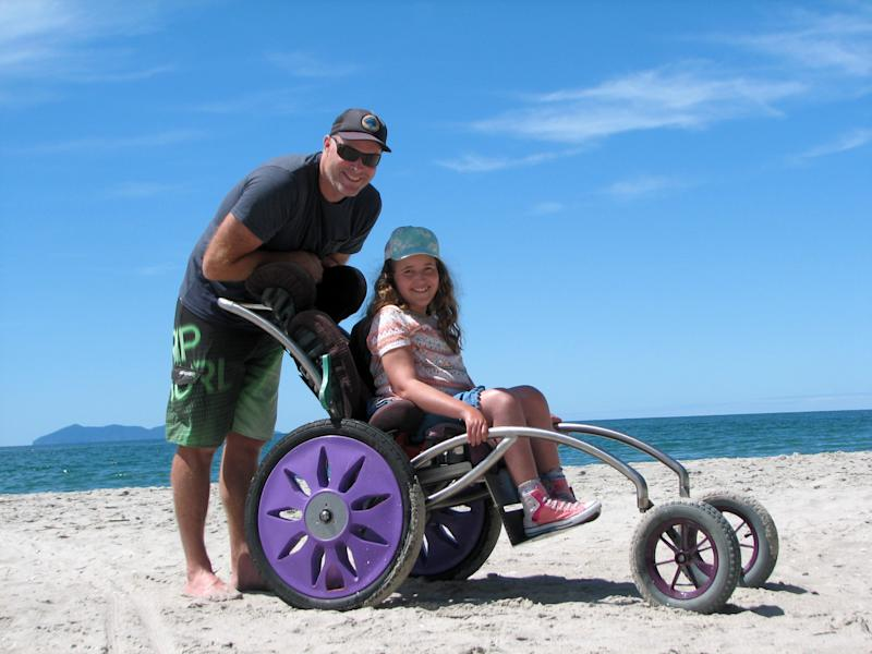 Stella is pictured with her father Hayden, 43, at the beach in a home made beach wheelchair. Source: Real Press