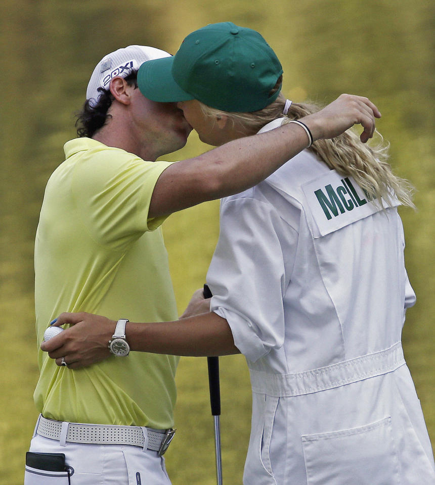 Rory McIlroy, of Northern Ireland, kisses his caddy and girlfriend tennis player Caroline Wozniacki following the par three competition before the Masters golf tournament Wednesday, April 10, 2013, in Augusta, Ga. (AP Photo/David J. Phillip)