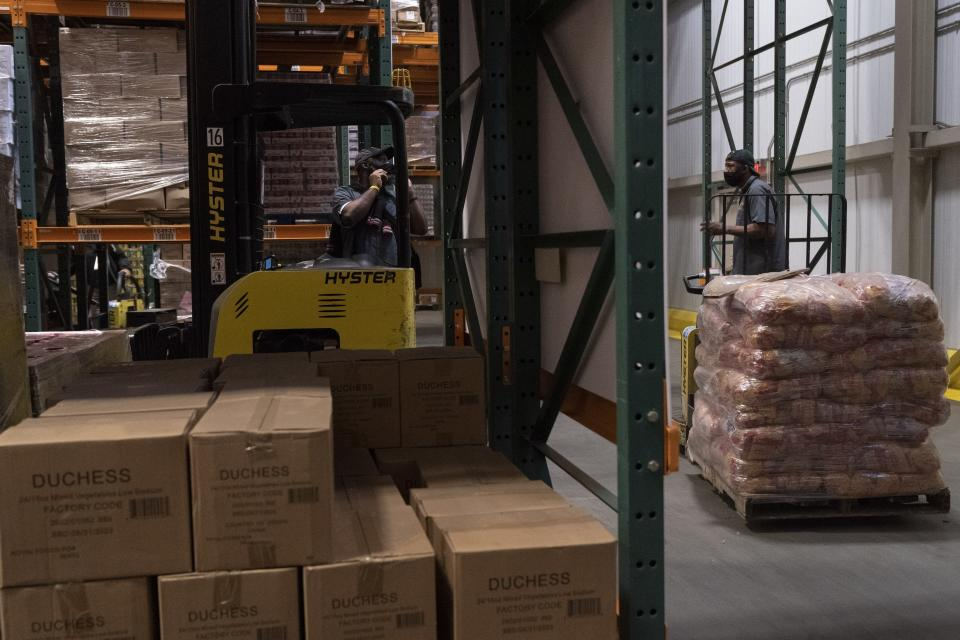 Workers load the warehouse with food items at The Capital Area Food Bank, Tuesday, Oct. 5, 2021, in Washington. (AP Photo/Jacquelyn Martin)