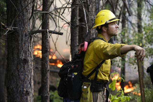 Firefighter Brandon Wenger stands along Highway 120 while monitoring a backburn during the Rim Fire near Yosemite National Park, Calif., on Tuesday, Aug. 27, 2013. Unnaturally long intervals between wildfires and years of drought primed the Sierra Nevada for the explosive conflagration chewing up the rugged landscape on the edge of Yosemite National Park, forestry experts say. The fire had ravaged the largest area in the Sierra's recorded history and one of the largest on record in California. (AP Photo/Jae C. Hong)