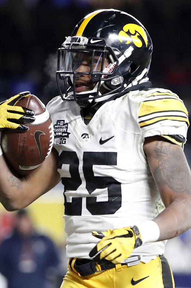 Iowa running back Akrum Wadley (25) scores a touchdown on a five yard run in the third quarter of the Pinstripe Bowl NCAA college football game Boston College, Wednesday, Dec. 27, 2017, in New York. Iowa defeated Boston College 27-20. Wadley was named the bowl game's Most Valuable Player. (AP Photo/Kathy Willens)