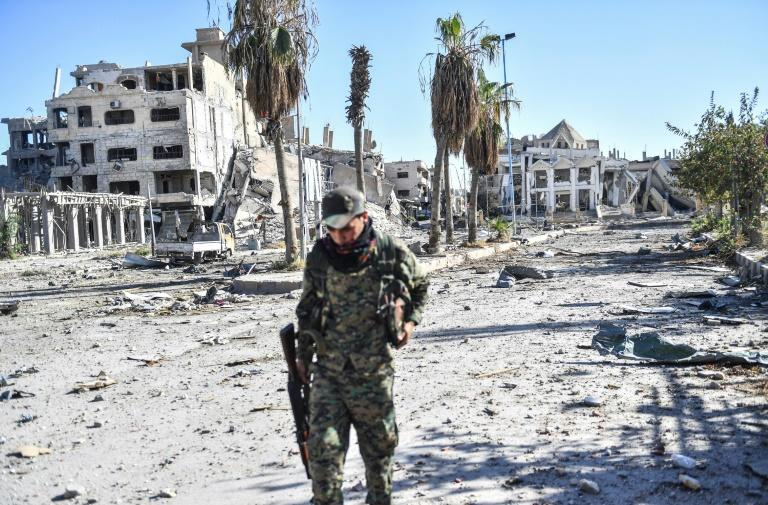 A fighter of the US-backed Syrian Democratic Forces walks down a heavily damaged a street in Raqa on October 18, 2017