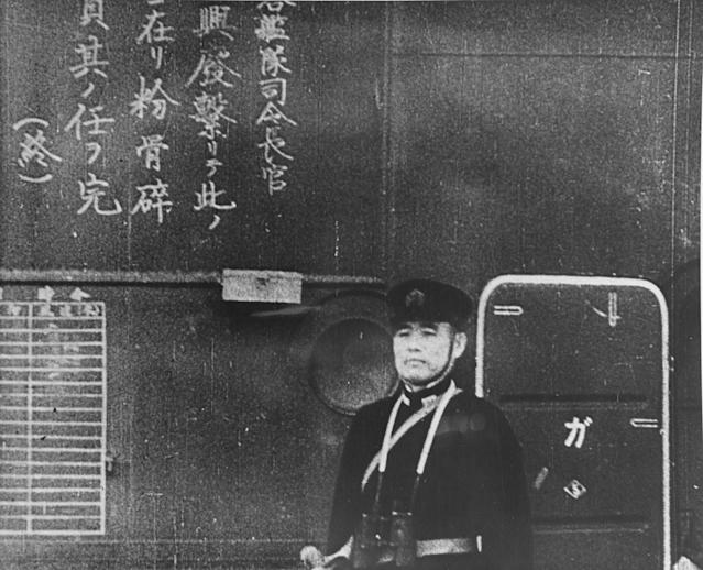 <p>An officer on the Japanese aircraft carrier Shokaku watches as planes take off to attack Pearl Harbor on Dec. 7, 1941. The Kanji inscription at left is a commander order to pilots to do their duty to destroy the enemy. (U.S. Navy/National Archives/Handout via Reuters) </p>