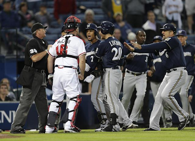 Milwaukee Brewers' Carlos Gomez (27) and Atlanta Braves catcher Brian McCann (16) are separated by home plate umpire Paul Nauert and Brewers' Jonathan Lucroy (20) as they exchange words following a home run by Gomez in the first inning of a baseball game Wednesday, Sept. 25, 2013 in Atlanta. Milwaukee Brewers third base coach Ed Sedar (6) rushes in at right. (AP Photo/John Bazemore)