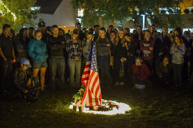 People gather around candles and a US flag during a vigil to pay tribute to the victims of a shooting in Thousand Oaks, California, on November 8, 2018