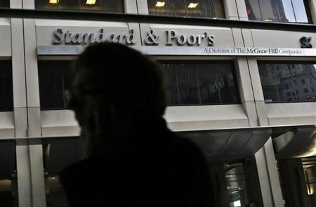 A man walks past the Standard and Poor's building in New York's financial district
