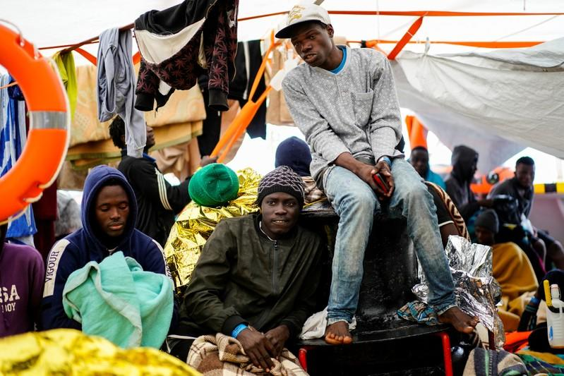 Migrants rest on board a NGO Proactiva Open Arms rescue boat in the central Mediterranean Sea