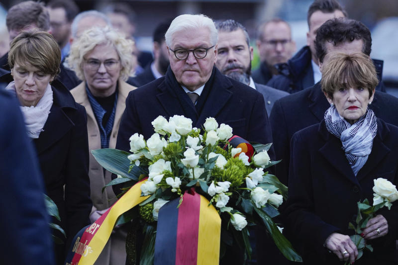 German president Frank-Walter Steinmeier, his wife Elke Buedenbender, left, and governor Volker Bouffier aarive to lay flowers at the hookah bar where several people were killed in Hanau, Germany, Thursday, Feb. 20, 2020. A 43-year-old German man shot and killed several people in different locations in a Frankfurt suburb overnight in attacks that appear to have been motivated by far-right beliefs, officials said Thursday. (Uwe Anspach/DPA via AP)