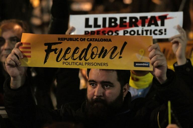 """Protesters hold banners reading """"Freedom for political prisoners"""""""
