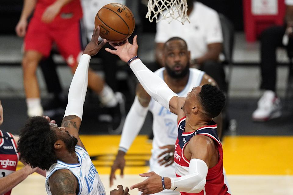 Washington Wizards guard Russell Westbrook, right, shoots as Los Angeles Lakers guard Wesley Matthews, left, defends and forward LeBron James watches during the first half of an NBA basketball game Monday, Feb. 22, 2021, in Los Angeles. (AP Photo/Mark J. Terrill)