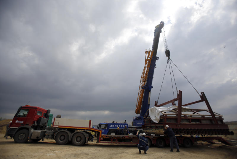 A crane lifts a complete skeleton of a mammoth, named Vika, secured in a specially made structure, at an open pit coal mine in Kostolac, 80 kilometers (50 miles) east of Belgrade, Serbia, Friday, April 11, 2014. Vika, a complete mammoth skeleton, discovered by Serbian archaeologists in 2009 inside the Kostolac open coal pit mine, was moved from the spot where it was found to a secure location because the pit mine threatened to endanger the safety of the remains. (AP Photo/Darko Vojinovic)