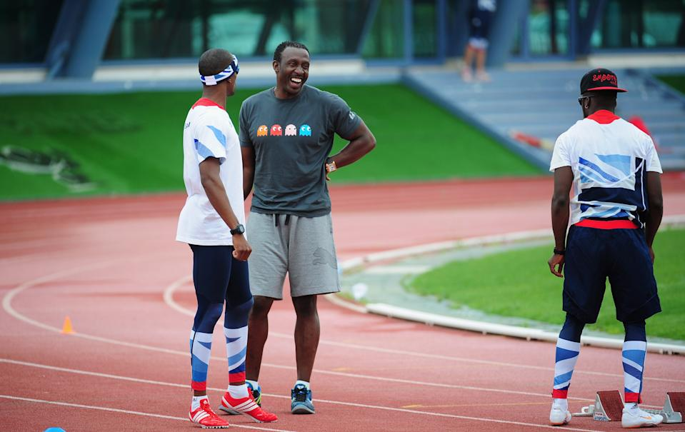 MONTE GORDO, PORTUGAL - JULY 25:  Coach Linford Christie (r) shares a joke with runner Conrad Williams during the Team GB Track and Field preperation camp at Monte Gordo Stadium on July 25, 2012 in Monte Gordo, Portugal.  (Photo by Stu Forster/Getty Images)