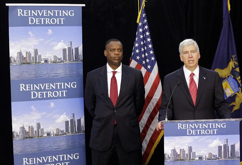 Michigan Gov. Rick Snyder, right, and State-appointed emergency manager Kevyn Orr address reporters during a news conference on Friday, July 19, 2013, in Detroit. On Thursday, Detroit became the largest city in U.S. history to file for bankruptcy when Orr asked a federal judge for municipal bankruptcy protection. (AP Photo/Carlos Osorio)