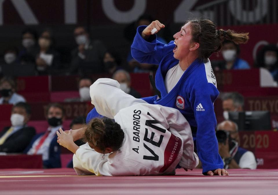 Catherine Beauchemin-Pinard raises her right fist in victory while her opponent is on the mat.