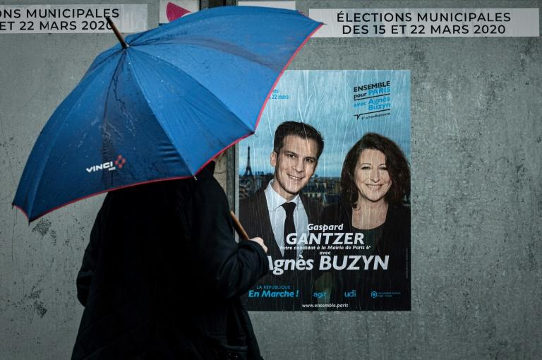 A man passes electoral poster ahead of the first round of the mayoral elections in Paris, as polls show Socialist incumbent Anne Hidalgo leading the race