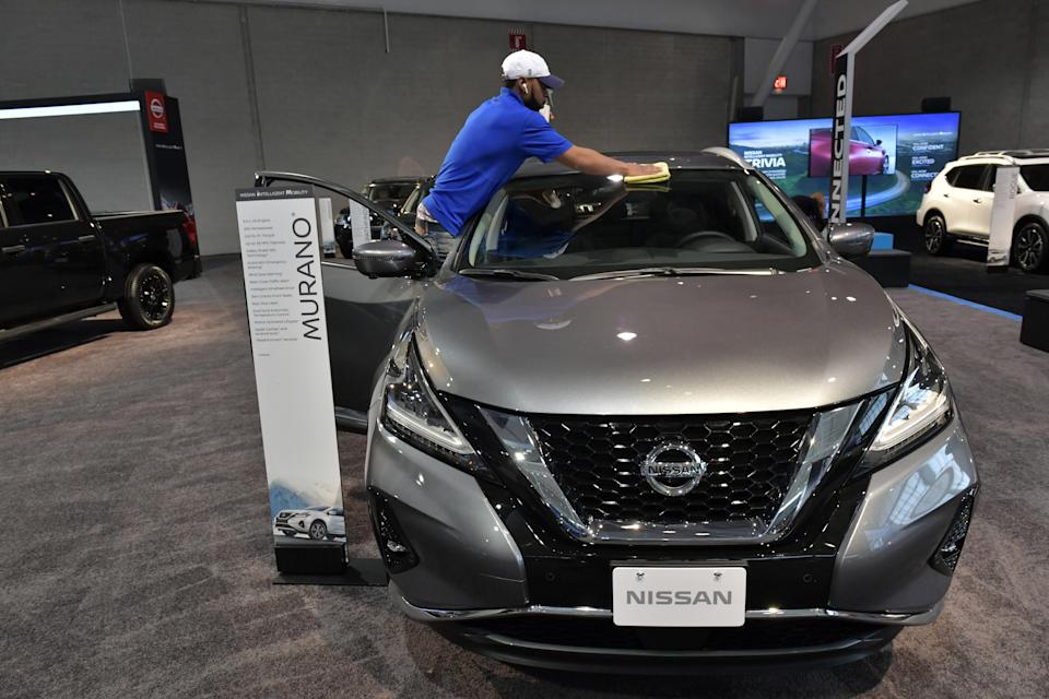 A worker readies a Nissan for exhibit at the 2020 New England Auto Show Press Preview