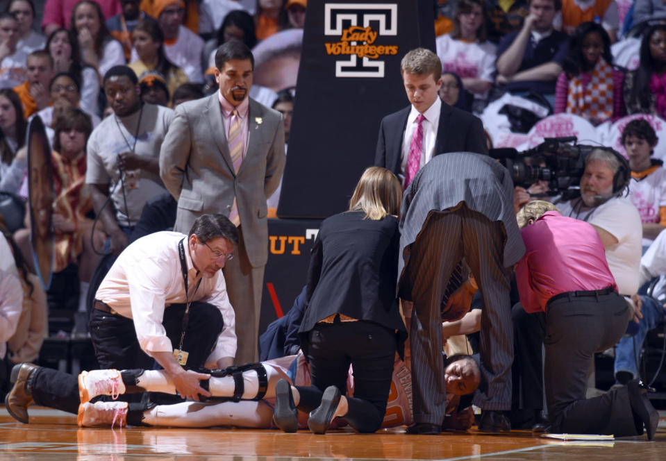 Tennessee's Isabelle Harrison, bottom middle, is attended to by orthopedic surgeon Dr. Greg Mathien, left, during an NCAA college basketball game against Kentucky, Sunday, Feb. 15, 2015, in Knoxville, Tenn. Tennessee won 72-58. (AP Photo/Patrick Murphy-Racey)