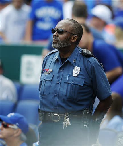 A Kansas City, Mo., police officer guards the entrance to the visitors dugout during an MLB American League baseball game between the Cleveland Indians and the Kansas City Royals at Kauffman Stadium in Kansas City, Mo., Thursday, July 4, 2013. (AP Photo/Orlin Wagner)