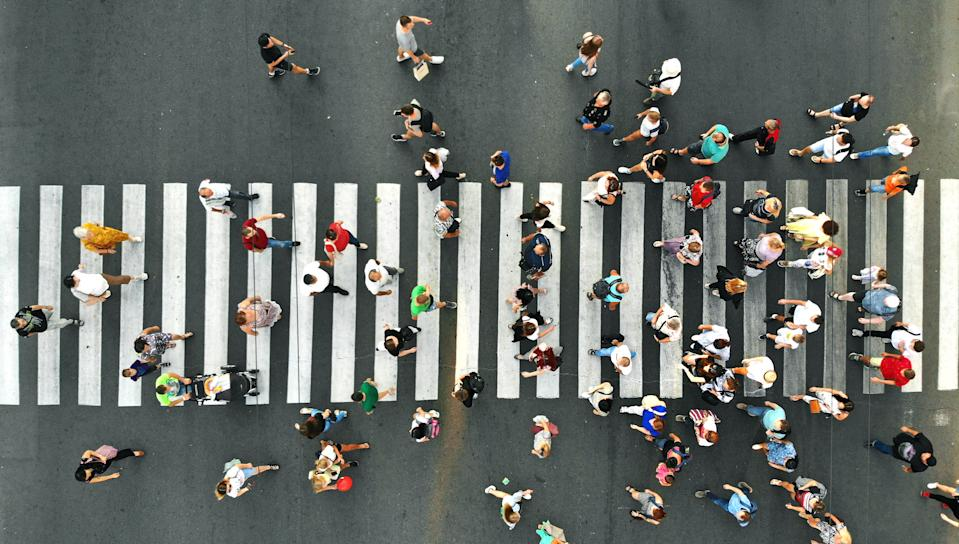 Aerial. People crowd. Many people going through the pedestrian crosswalk. Top view.