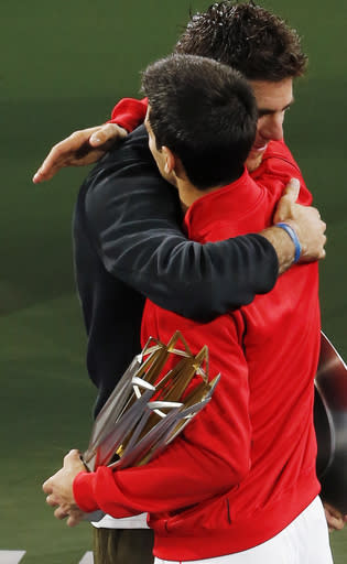 Serbia's Novak Djokovic, in red, and Juan Martin del Potro of Argentina, in black, embrace each other during the award ceremony of the Shanghai Masters tennis tournament at Qizhong Forest Sports City Tennis Center, in Shanghai, China, Sunday, Oct. 13, 2013. Djokovic won 6-1, 3-6, 7-6. (AP Photo/Eugene Hoshiko)