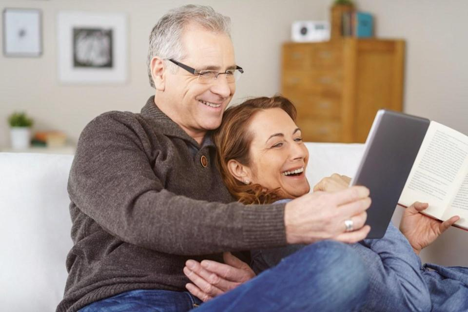 Affectionate middle-aged couple relaxing on a sofa together at home laughing at something on a tablet computer, natural and spontaneous