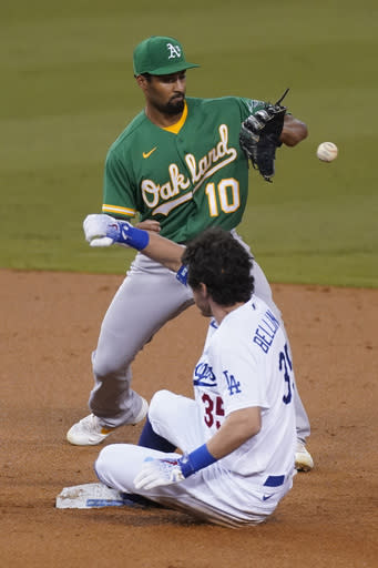 Los Angeles Dodgers' Cody Bellinger doubles to second base ahead of a throw to Oakland Athletics shortstop Marcus Semien during the first inning of their baseball game Tuesday, Sept. 22, 2020, in Los Angeles. (AP Photo/Ashley Landis)
