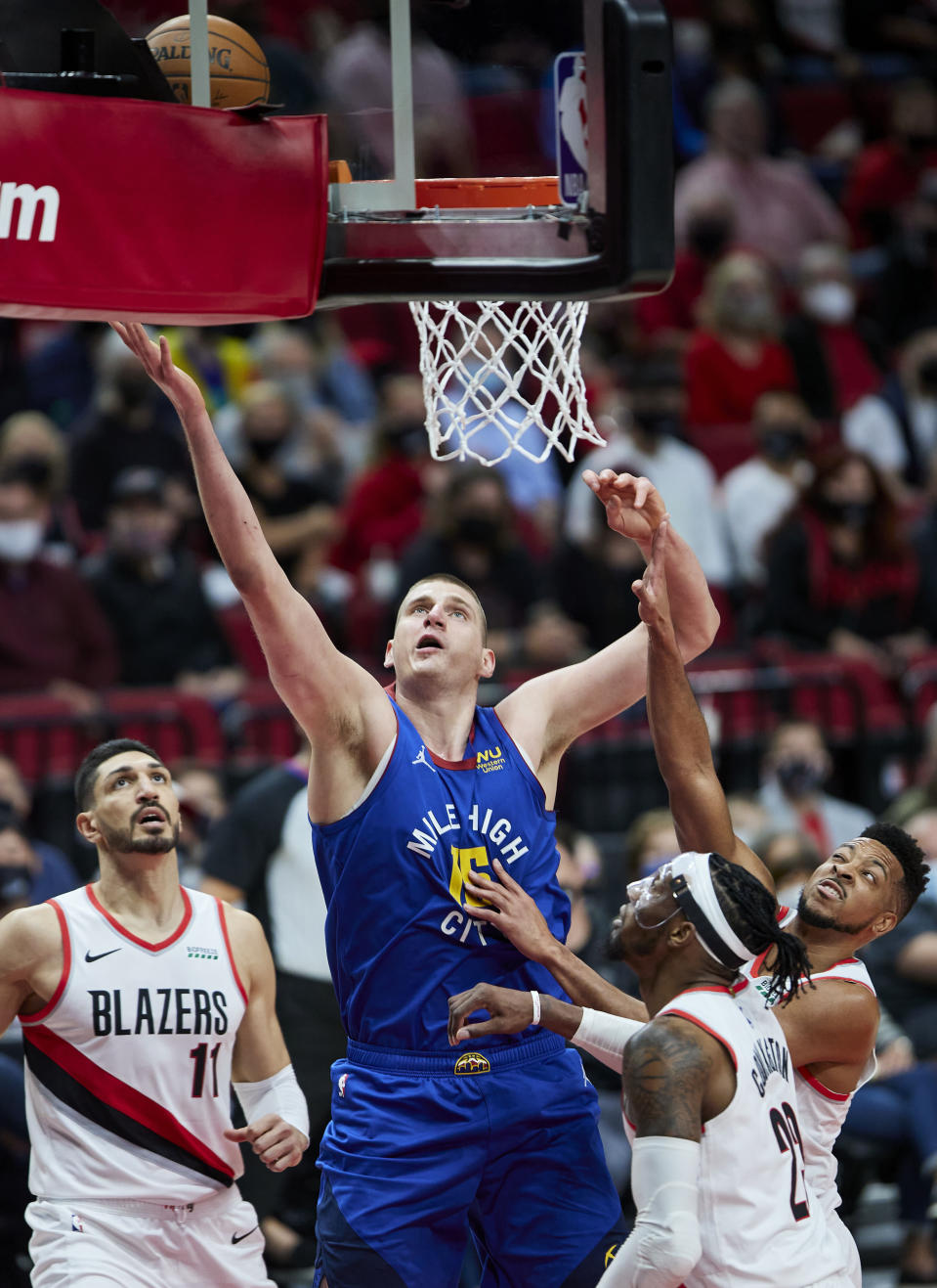 Denver Nuggets center Nikola Jokic, center, shoots over Portland Trail Blazers guard CJ McCollum, right, forward Robert Covington, second from right, and center Enes Kanter, left, during the first half of Game 3 of an NBA basketball first-round playoff series Thursday, May 27, 2021, in Portland, Ore. (AP Photo/Craig Mitchelldyer)