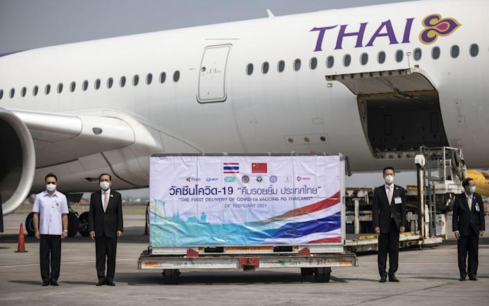 Prayuth Chan-Ocha, Thailand's prime minister, second left, next to an Envirotainer AB refrigerated shipping container with the first shipment of Sinovac Biotech Ltd. coronavirus vaccine as it is unloaded from a Thai Airways cargo flight at Suvarnabhumi Airport in Bangkok, - Andre Malerba/Bloomberg