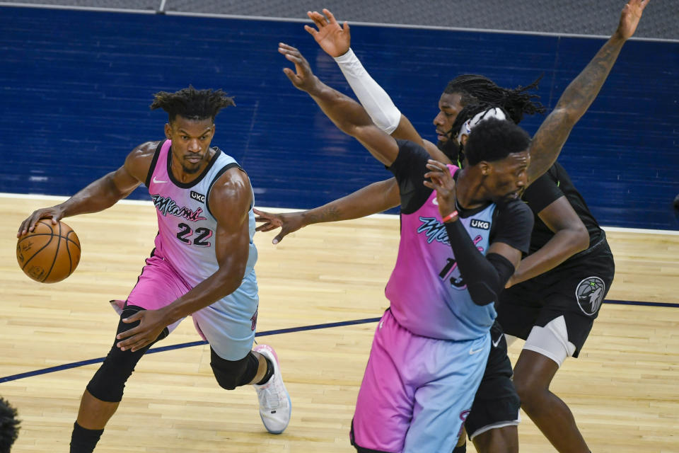 Miami Heat forward Jimmy Butler(22) drives past a crowd of Minnesota Timberwolves defenders as Heat center Bam Adebayo, right front, tries to set a pick during the first half of an NBA basketball game Friday, April 16, 2021, in Minneapolis. (AP Photo/Craig Lassig)