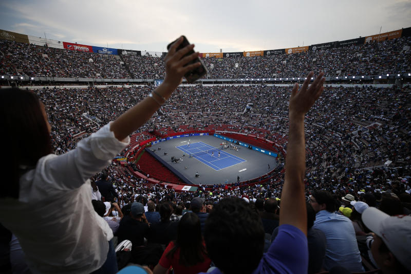 Spectators wave from the stands as brothers Bob and Mike Bryan of the U.S., left, take on Mexico's Miguel Angel Reyes Varela and Santiago Gonzalez in an exhibition doubles tennis match in the Plaza de Toros bullring in Mexico City, Saturday, Nov. 23, 2019. Roger Federer of Switzerland and Germany's Alexander Zverev were also to face off in the converted bullring Saturday, the fourth stop in a tour of Latin America by the tennis greats.(AP Photo/Rebecca Blackwell)