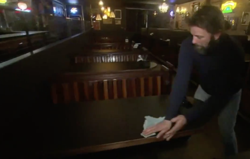 Jeff Griffiths, the owner of Sneaky Pickle in Adelaide, wipes down tables in his restaurant.