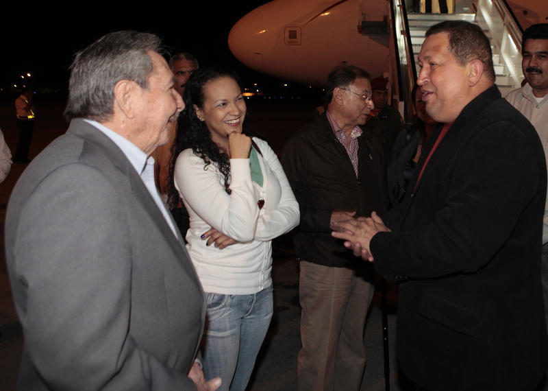 In this photo released by Miraflores Press Office, Venezuela's President Hugo Chavez, right, accompanied by one of his daughters, Rosa, second from left, is welcomed by Cuba's President Raul Castro, left, upon his arrival to Havana, Cuba, Friday, Feb. 24, 2012. Chavez is in Cuba for urgent surgery to remove a tumor he says is probably malignant. (AP Photo/Miraflores Press Office/Marcelo Garcia)
