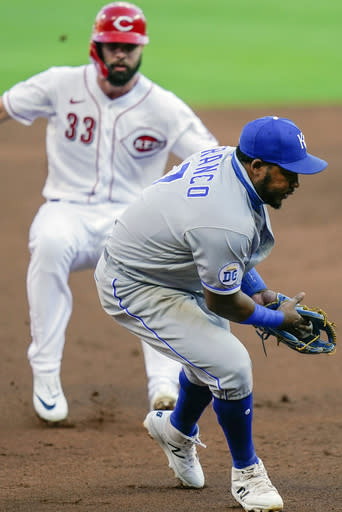 Kansas City Royals third baseman Maikel Franco (7) fields the ball before tagging our Cincinnati Reds left fielder Jesse Winker (33) during the third inning of a baseball game at Great American Ballpark in Cincinnati, Tuesday, Aug. 11, 2020. (AP Photo/Bryan Woolston)