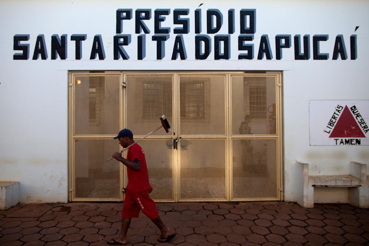 In this photo taken Friday, July 6, 2012, an inmate walks past the prison entrance in Santa Rita do Sapucai, Brazil. An innovative program allows inmates at this medium-security prison to shave days off their sentence in exchange for riding stationary bikes hooked up to converted car batteries that are used to illuminate Santa Rita do Sapucai's town square. (AP Photo/Felipe Dana)