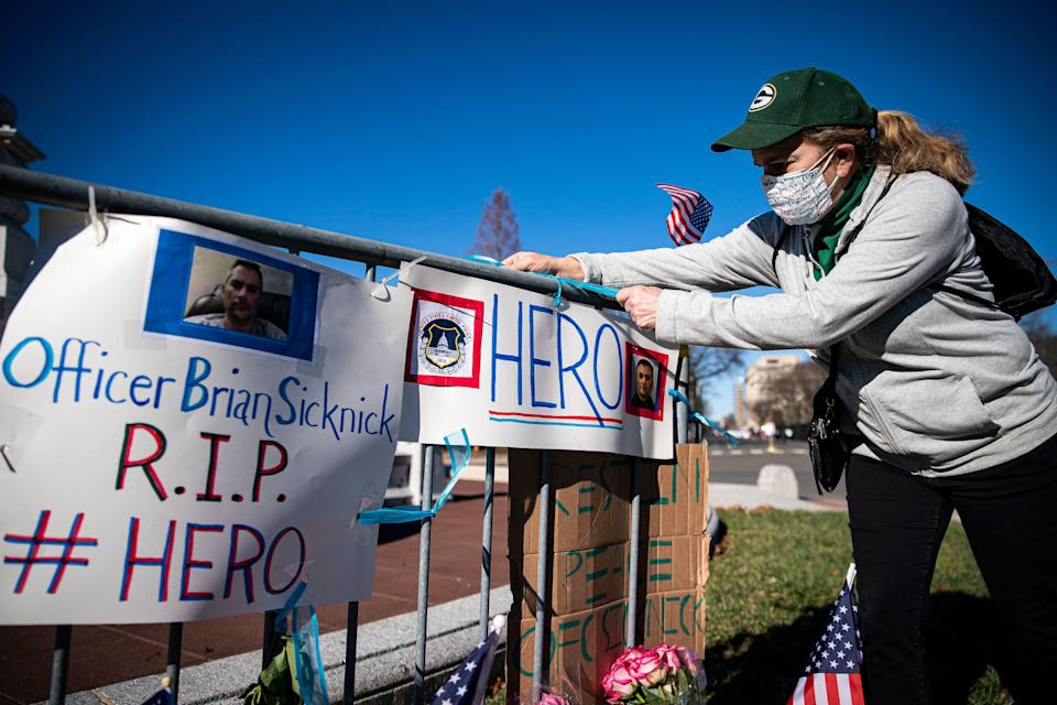 Anne Seymour, a crime victim advocate, creates a makeshift memorial Jan. 9 in Washington for U.S. Capitol Police officer Brian Sicknick, who was fatally injured when a pro-Trump mob stormed the Capitol.