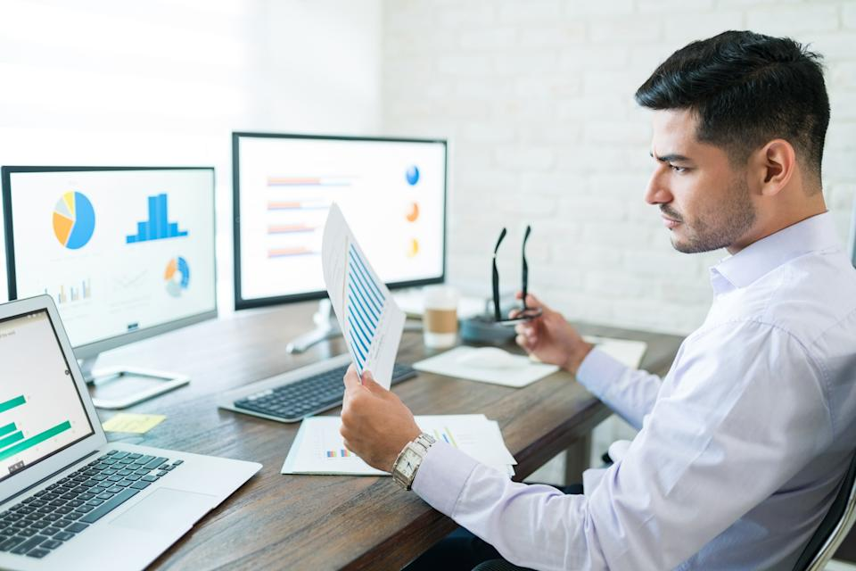 Young male sales professional analyzing chart while holding paper at desk.