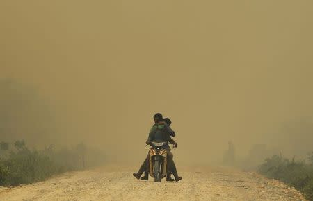 Villagers ride a motorcycle in a haze hit Dumai, in Indonesia's Riau province in this June 21, 2013 file photograph. REUTERS/Beawiharta/Files
