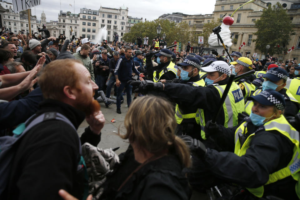 """LONDON, ENGLAND - SEPTEMBER 26: Protesters clash with police officers during a """"We Do Not Consent"""" anti-lockdown rally at Trafalgar Square on September 26, 2020 in London, England. Thousands of anti-mask demonstrators protested in Trafalgar Square after the British government imposed tighter coronavirus laws this week.  (Photo by Hollie Adams/Getty Images)"""
