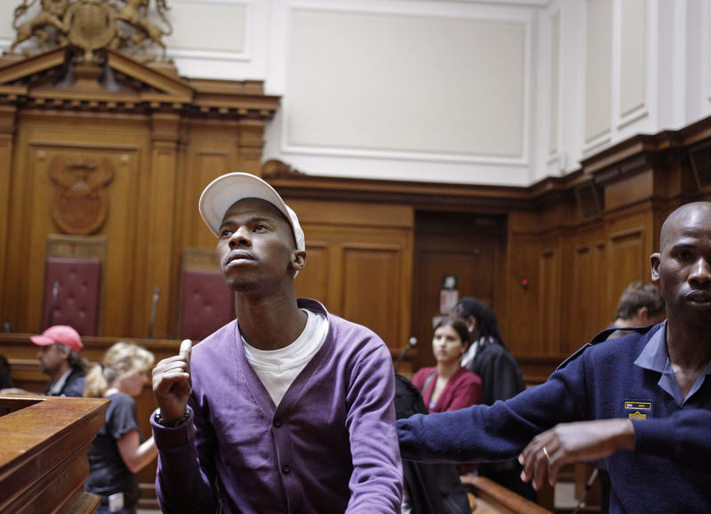 "Xolile Mngeni, left, shows his family members a thumbs up after being sentenced in court at Cape Town, South Africa, Wednesday, Dec. 5,  2012. A South African judge sentenced the triggerman in the 2010 honeymoon slaying of a Swedish bride to life in prison Wednesday, calling the shooter ""a merciless and evil person"" who deserved the maximum punishment for his crime. Prosecutors say the newlywed's British husband orchestrated the November 2010 killing. Judge Robert Henney did not hold back his contempt while sentencing Xolile Mngeni for the killing of 28-year-old Anni Dewani. Henney said that the shooter showed no remorse. (AP Photo/Schalk van Zuydam)"