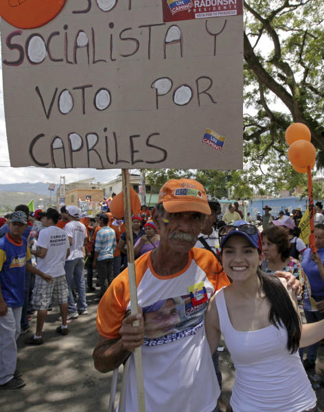 """In this Sept. 1, 2012 photo, a man and his daughter pose with a poster that reads in Spanish; """"I'm a socialist and will vote for Capriles,"""" at a campaign rally in Miranda, Venezuela. From single mothers to construction workers, a segment of President Hugo Chavez supporters have been turning away from the president and instead considering new leadership. They've become key to the Oct. 7 presidential vote and to opposition presidential candidate Henrique Capriles' strategy. (AP Photo/Fernando Llano)"""