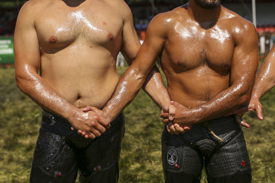Wrestlers, doused in olive oil, greet each other as they are introduced to the crowds during the 660th instalment of the annual Historic Kirkpinar Oil Wrestling championship, in Edirne, northwestern Turkey, Saturday, July 10, 2021. Thousands of Turkish wrestling fans flocked to the country's Greek border province to watch the championship of the sport that dates to the 14th century, after last year's contest was cancelled due to the coronavirus pandemic. The festival, one of the world's oldest wrestling events, was listed as an intangible cultural heritage event by UNESCO in 2010. (AP Photo/Emrah Gurel)